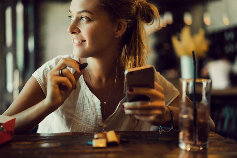 WhatsApp-Nachrichten, die man dem Partner gerne verheimlichen darf: Eine Frau in einer Bar mit einem Handy in der Hand