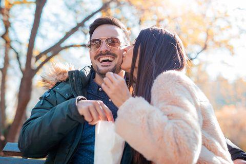In einer Beziehung: Eine Frau küsst ihren lachenden Mann auf die Wange