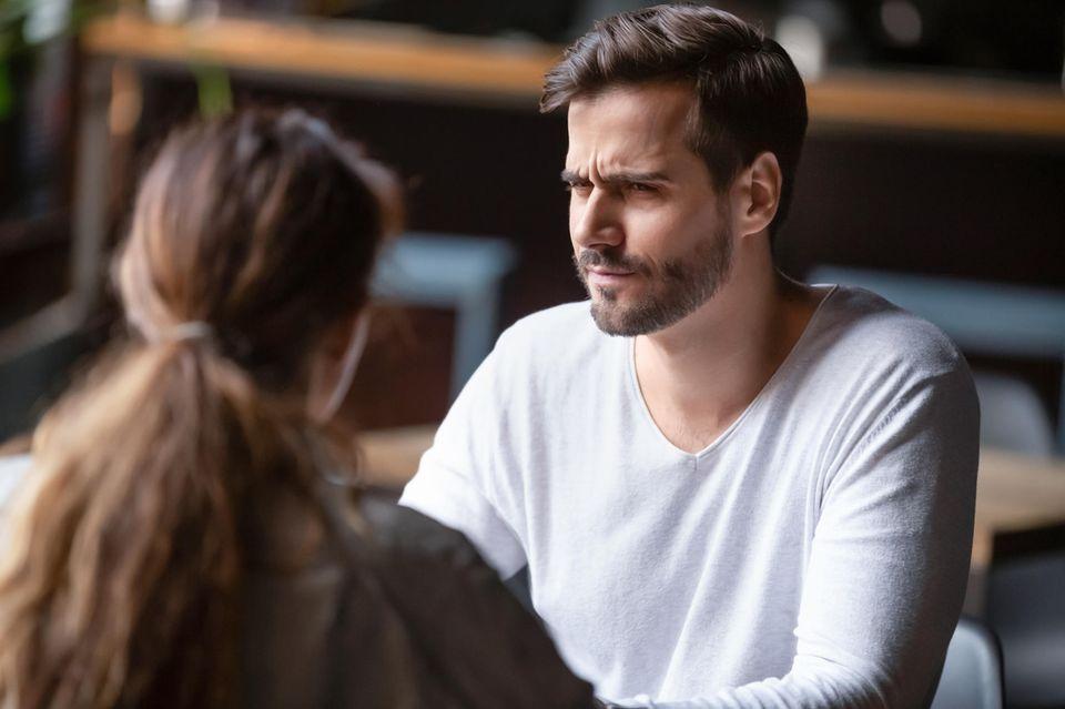 LoveScout24-Umfrage: Ein skeptischer Mann schaut sein Date an