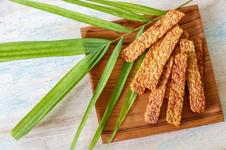 Tempeh zubereiten: Tempeh gebraten auf Holzbrett