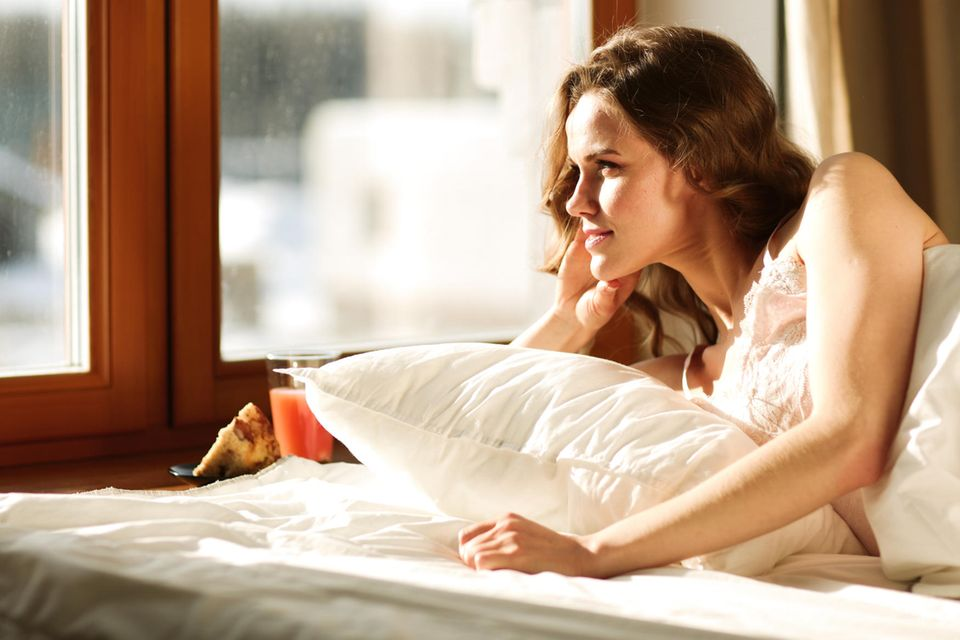 Federbett-Lunge: Frau liegt im Bett