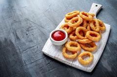 Zwiebelringe: Onion Rings auf einem Brett