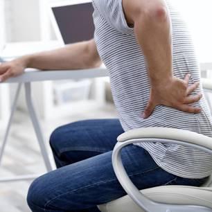 Lumbalgie: Frau hält sich den Rücken