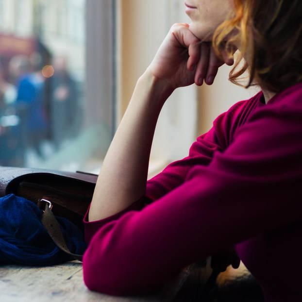 Beziehungsunfähigkeit: Welche Rolle spielen die Eltern?: Nachdenkliche Frau vor Fenster