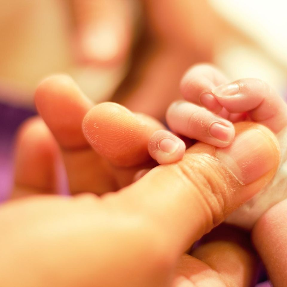 Fetus in fetu: Symbolbild Mutter Baby halten Händchen