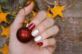 Fingernägel-Design: Frauenhand hält Weihnachtskugel
