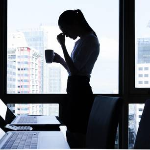 Stressmanagement: Gestresste Frau im Büro