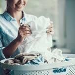Diese Kleidungsstücke solltet ihr nicht täglich waschen: Frau mit Wäschekorb