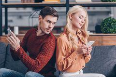 Digitale Eifersucht: Pärchen mit Smartphones, Freund schaut auf das Handy der Freundin