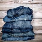 Jeans färben: Jeans in unterschiedlichen Blautönen vor Holzwand