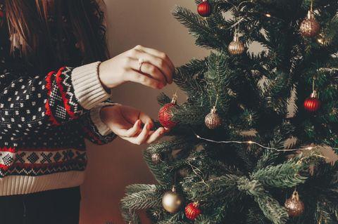 Weihnachtsbaum-Fehler: Frau schmückt Baum