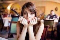 Emotionales Essen: Frau hält Besteck in den Händen und schaut erschrocken