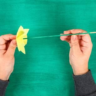 Blumen basteln: Grünes Holzstäbchen in Papierblume befestigen