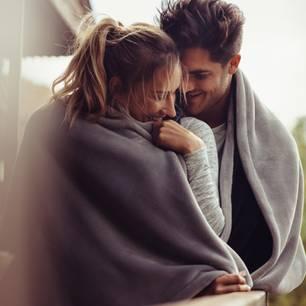 Sex auf dem Balkon: Pärchen auf einem Balkon in eine Decke gewickelt