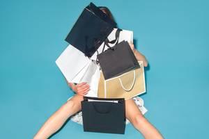Frau hinter Einkaufstaschen
