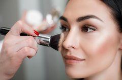 Bronzer auftragen: Frau wird geschminkt
