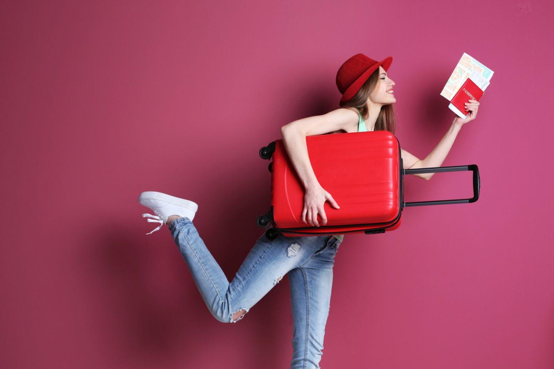 Fernweh: Frau hält Koffern und Reisedokumente in den Händen