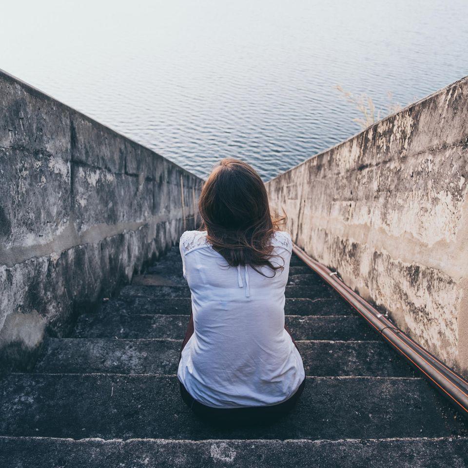 Angst: Frau sitzt auf einer Treppe