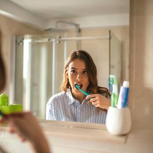 Frau putzt Zähne im Spiegel