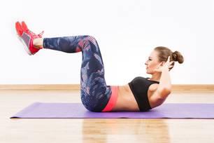 Frau macht Crunches mit Beinen angewinkelt