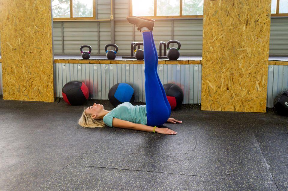 Frau beim Training mit den Beinen in der Luft