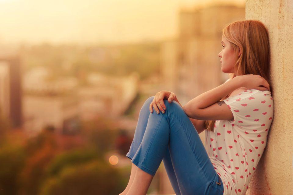 Heimweh: Junge Frau sitzt auf Balkon beim Sonnenuntergan