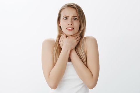 Pickel am Hals: Frau hält sich die Hände vor den Hals