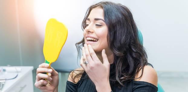 Gelbe Zähne: Frau betrachtet ihr Zähne im Spiegel