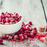 Rosenöl: Rosenblüten im Mörser und Flasche mit Rosenöl