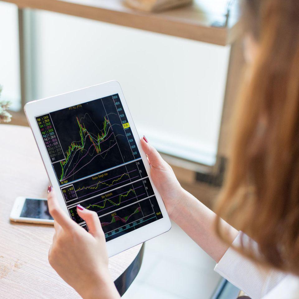 Wie kauft man Aktien?: Frau mit Aktien auf Tablet abgebildet