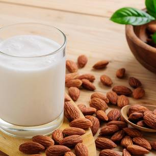 Mandemmilch: Milch im Glas mit Mandeln drumherum