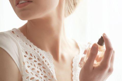 Frau sprüht sich mit Parfum ein