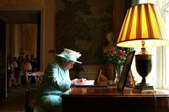 Queen Elizabeth II. unterschreibt etwas