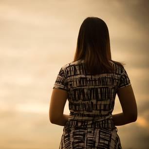 Frau allein, schaut in die Ferne