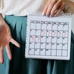Tipps gegen verspätete Periode: Frau hält einen Kalender mit Fragezeichen