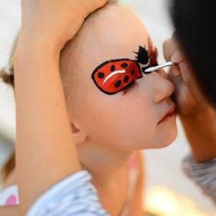 Marienkäfer schminken: Mädchen wird geschminkt
