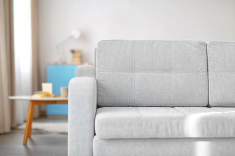 So reinigst du dein Sofa richtig: Frau putzt ein Sofa