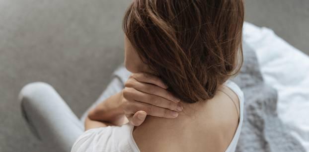 Nackenschmerzen: Frau hält sich den Nacken