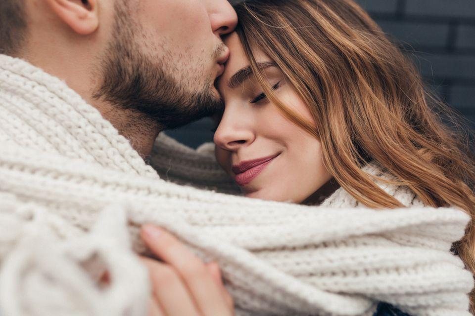 Kuss auf die Stirn: Mann küsst Freundin auf die Stirn