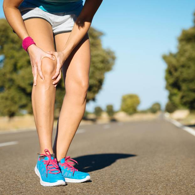 Frau hält sich vor Schmerzen das Knie