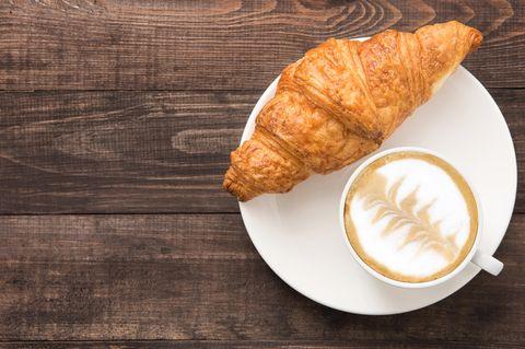 Croissant und Milchkaffee auf Teller