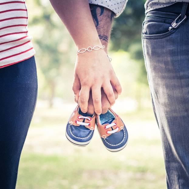 Schwangerschaft verkünden: Paar hält Babyschuhe in der Hand
