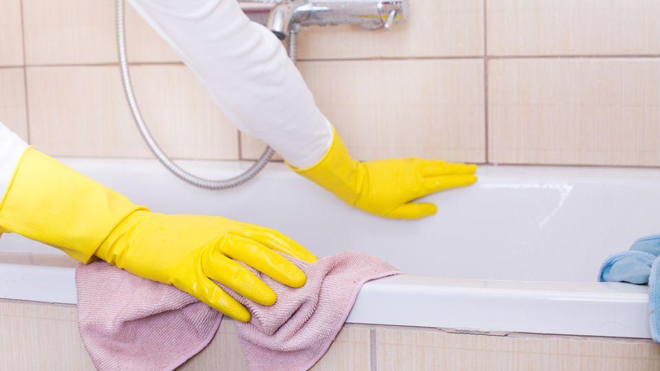 Frau putzt Badewanne mit Lappen