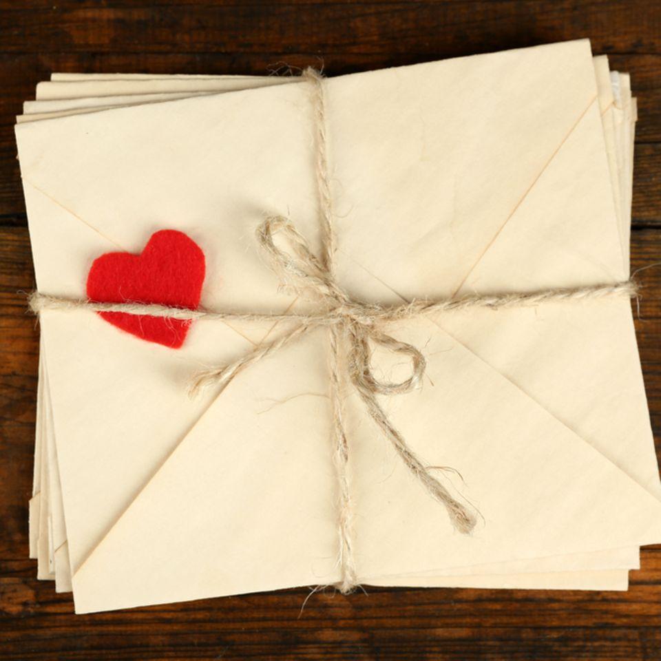 Liebesbrief schreiben: Briefstapel und ein Dekoherz