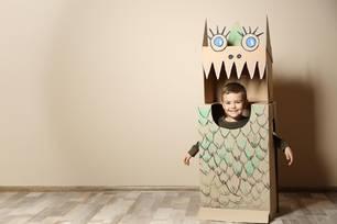 Kind in Drachenkostüm aus Pappkartons