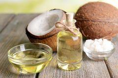Flasche Kokosöl und Kokosnüsse