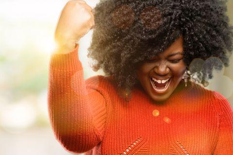 Innere Stärke: Frau lacht und macht starke Geste