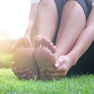Frau auf Wiese hält sich die Füße