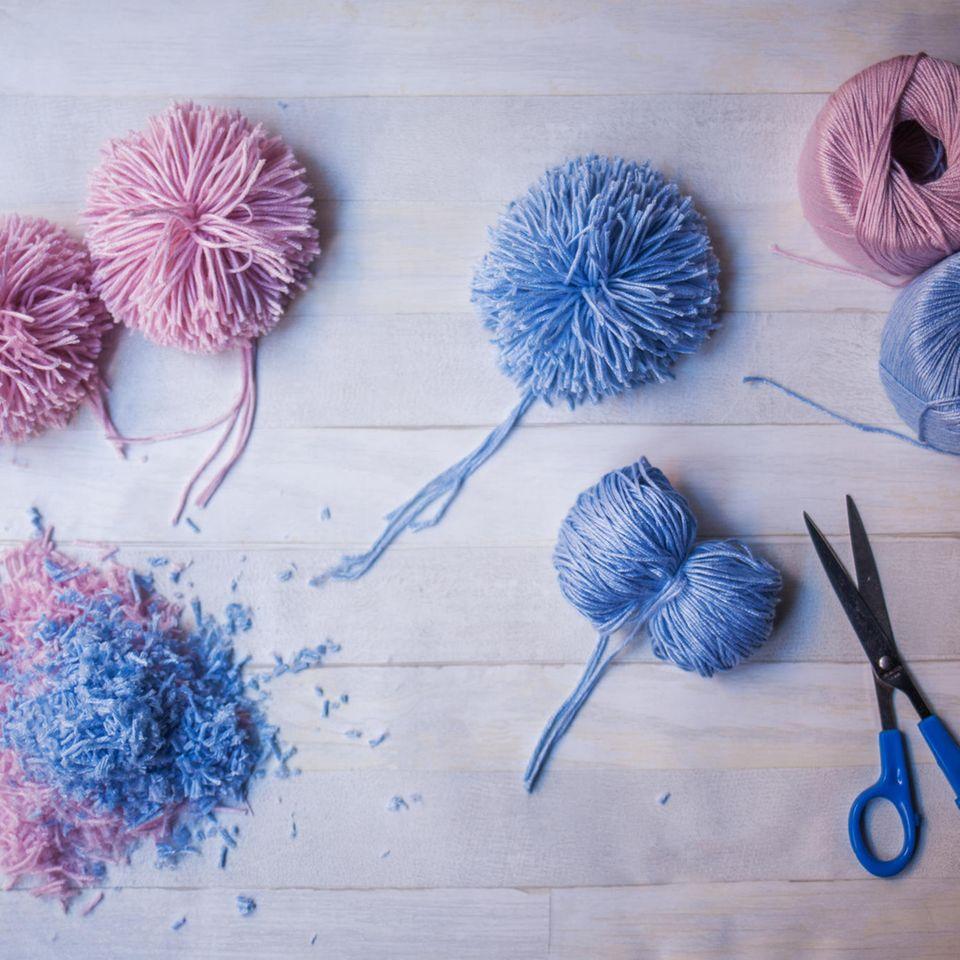 Pompoms aus pinker und blauer Wolle