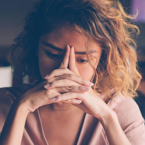 Frau im Cafe mit Händen vor dem Gesicht